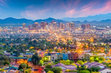 Downtown Phoenix, Arizona cityscape at dusk with mountains and sunset..