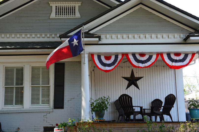 The Texas flag flies from the front porch of an arts and crafts home in the Dallas neighborhood of Lower Greenville
