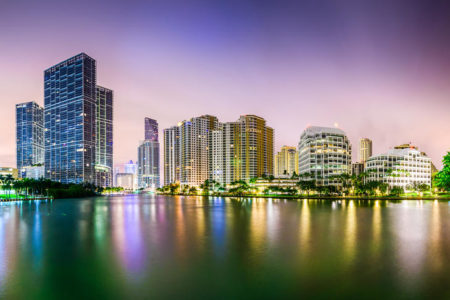 Downtown Miami, Florida city skyline with lights on water and purple sky at dusk.