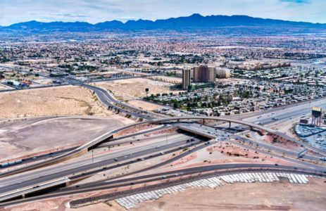 Aerial view of a traffic on freeway interchange in Las Vegas, Nevada with mountains on sunny day.