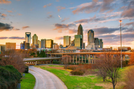 Skyline of Charlotte, North Carolina at dusk with green grass and clouds in sky.