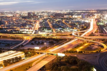 Highway interchange near downtown Dallas, Texas at night with city lights.