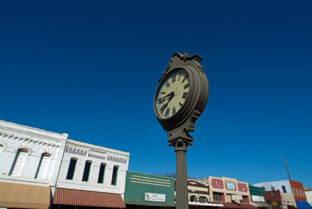 Public clock in downtown Plano, Texas with buildings and blue sky.