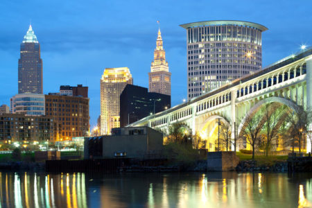Downtown skyline of Cleveland, Ohio at night with Cuyahoga River and city lights.