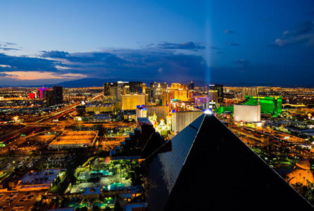 Aerial view of Las Vegas Strip in Nevada with Luxor Hotel at night with lights.