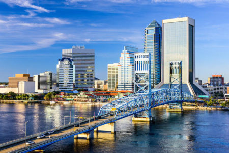 Downtown city skyline of Jacksonville, Florida at John T. Alsop Jr. Bridge on St. Johns River with blue sky.