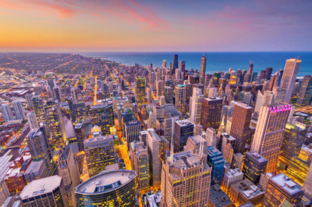 Downtown skyline of Chicago, Illinois at dusk with sunset and Lake Michigan.
