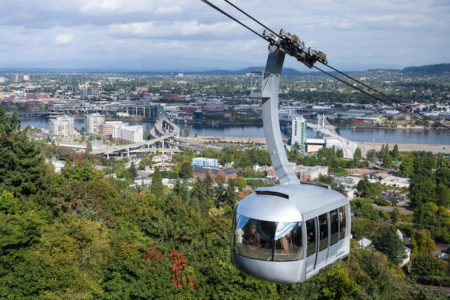 Aerial tram overlooking Portland, Oregon with green trees and gray skies.