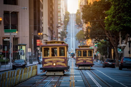 Historic traditional cable cars riding on famous California Street during summer morning light at sunrise in San Francisco, California.