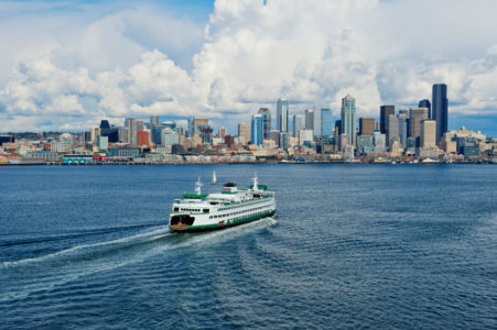 Aerial view of ferry with Seattle, Washington skyline with clouds in sky.