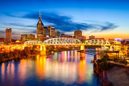 Nashville, TeDowntown city skyline of Nashville, Tennessee with bridge over water at dusk..