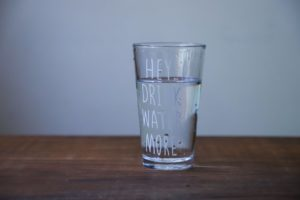 glass of water sitting on brown table, drink more water, water glass, wooden table