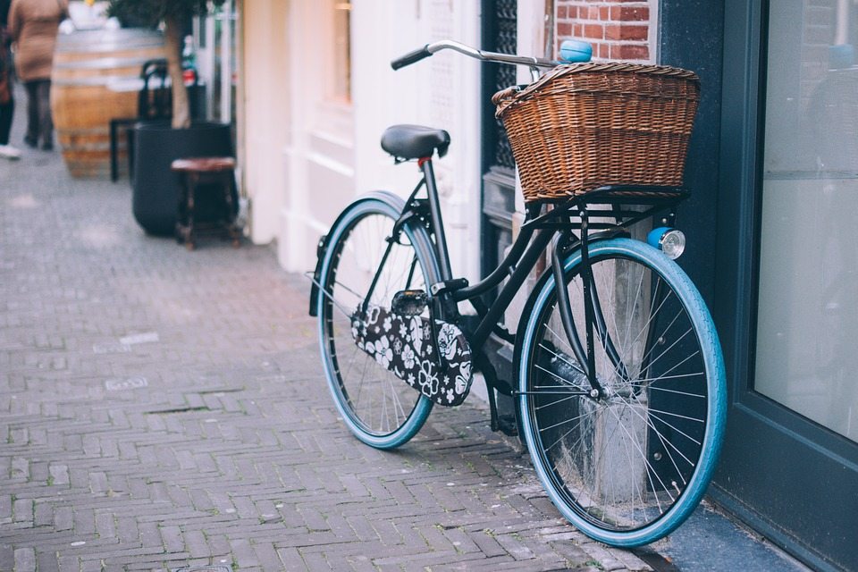 A black and blue bike with a basket is propped up against a wall outside