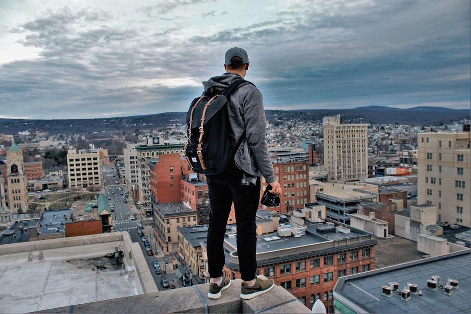 A millennial stands on a rooftop with a backpack on and holding a camera, looking over a city.