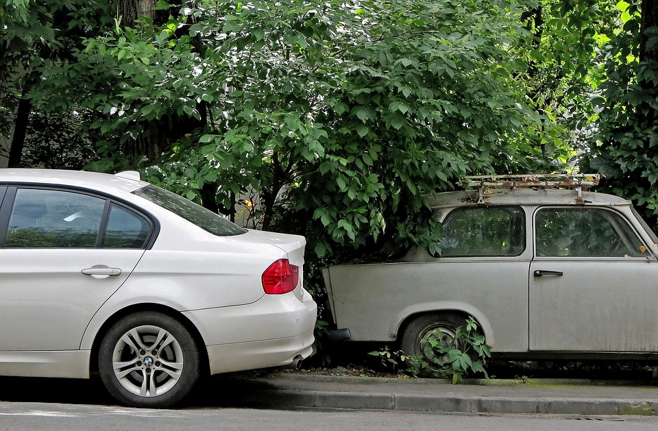 An image of a new car driving past an older automobile.
