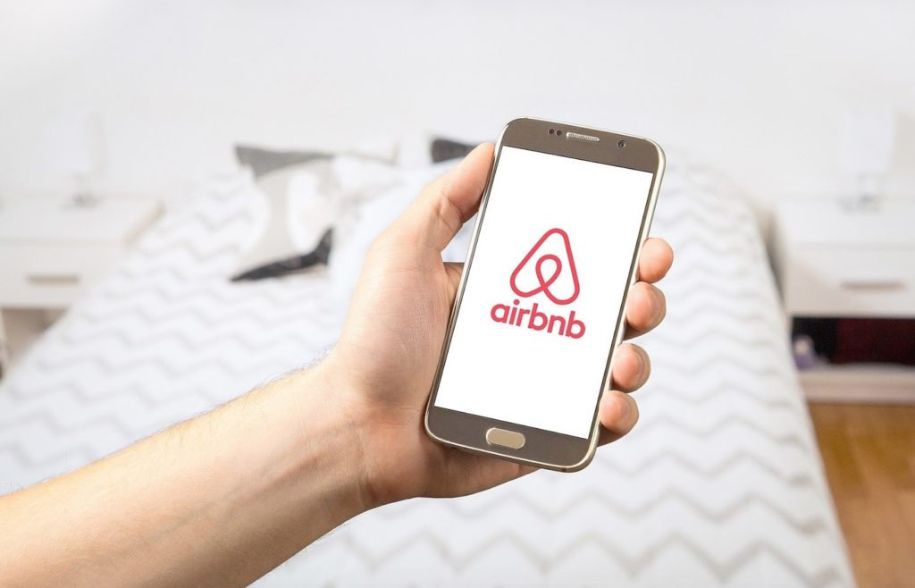 airbnb image on smartphone in bedroom of a rental property