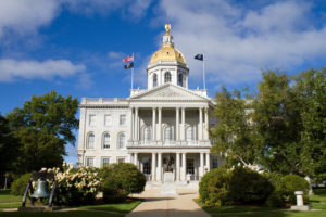 The state house capital building of New Hampshire is located in the city of Concord, NH, USA with surrounding grounds.