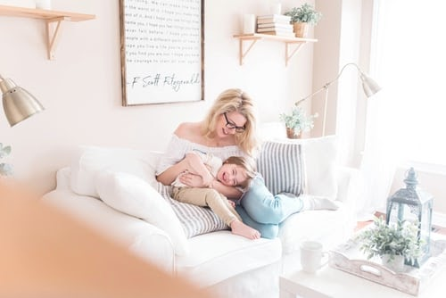 mother with blonde hair sitting on white couch snuggling with child, blue striped pillow