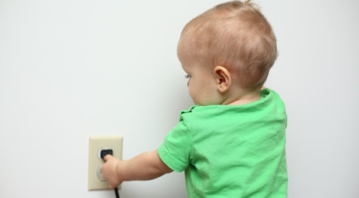 baby in green shirt trying to touch a black cord plugged into a beige electrical outlet, white wall behind