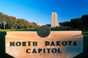 State Capitol of North Dakota, Bismarck during fall with orange and green leaves against blue sky