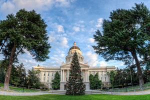Wide angle view of Capital Christmas tree in front of California State Capitol building in Sacramento with green trees and clouds in sky.