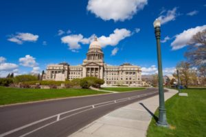 State capitol of Boise, Idaho during summer with green grass lining boulevard and blue sky with clouds.