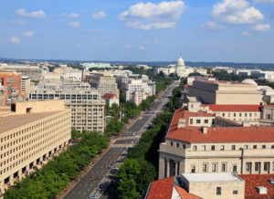 Aerial view of Washington DC along Pennsylvania Avenue during summer with green trees and blue sky with clouds