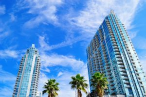 tall condo buildings, palm trees, blue sky, white clouds, windows