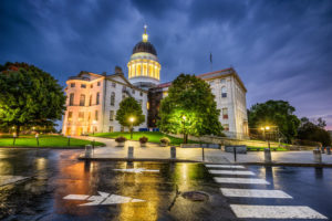 Maine State House in Augusta, Maine at night with rain on sidewalk crossing and street lights