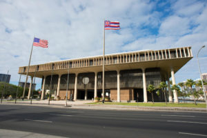Hawaii State Capital building in Honolulu, Hawaii against clouds in sky with street and flags