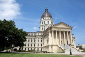 Kansas State Capitol located in Topeka, Kansas during summer with green grass and blue sky.