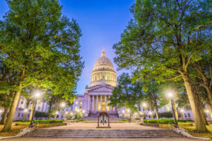 West Virginia State Capitol in Charleston in evening with sidewalk lights and green trees