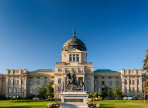 Montana's State Capitol Building, Helena, Montana with Thomas Meagher Statue during summer with green grass and blue sky
