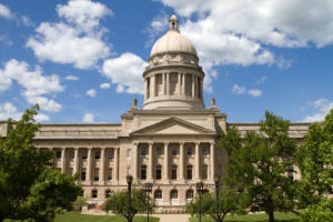 Kentucky State Capitol in Frankfort, Kentucky against a blue sky filled with clouds during summer with green trees.