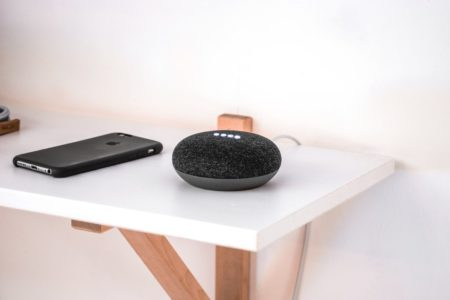 black google home with black smart phone next to it, sitting on white table with white wall