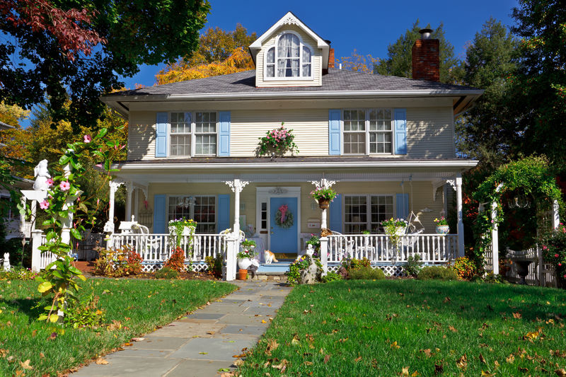 Huge country style home, white fenced in porch, blue shutters
