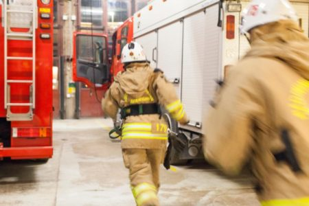 Firefighter running towards fire engine