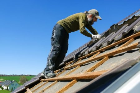 roofer laying tile on the roof.