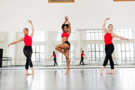 Low angle view of dancers in dance studio practicing in front of mirror