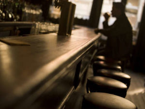 Bar with man whose health insurance coverage has been denied due to a DUI or alcohol abuse