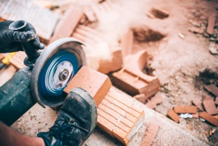 Industrial worker cutting through bricks. Professional brickmason using grinder at building houses