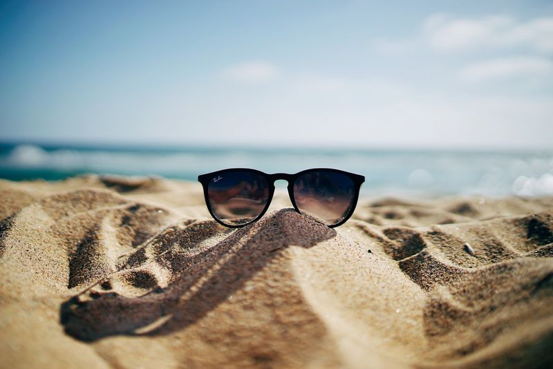 sunglasses sitting in sand, beach, blue sky, ocean, water, summer, summer time, hot, warm