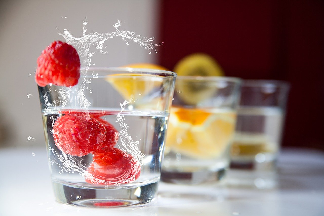 Raspberry and lemon in glass of water