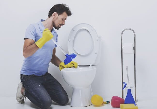 man with plunger plunging toilet, yellow rubber gloves, sponge, white toilet