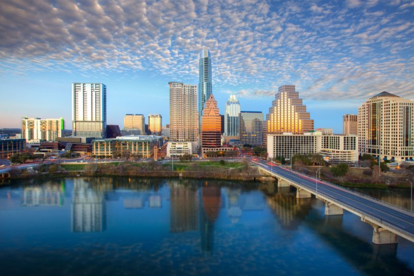 The Austin Skyline in Austin, Texas, shines on a late afternoon. The iconic Austin highrises are reflected in Lady Bird Lake.