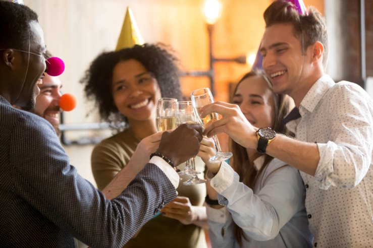 Happy black and white friends clinking glasses celebrating party
