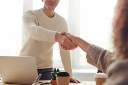 man in white shirt shaking hands with woman brown shirt, desk, coffee cups