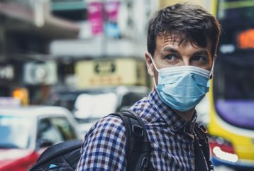 Man on busy street wearing a face mask.