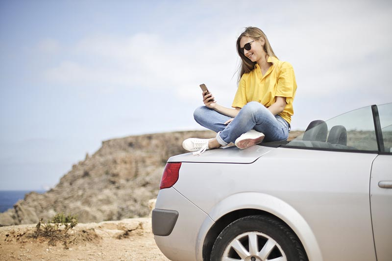 https://res.cloudinary.com/quotellc/image/upload/insurance-site-images/usinsuranceagents-live/2019/09/girl-car-phone.jpg