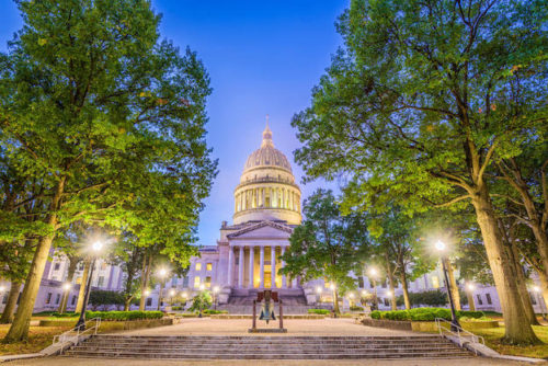 West Virginia State Capitol in Charleston, West Virginia in evening with lights and green trees